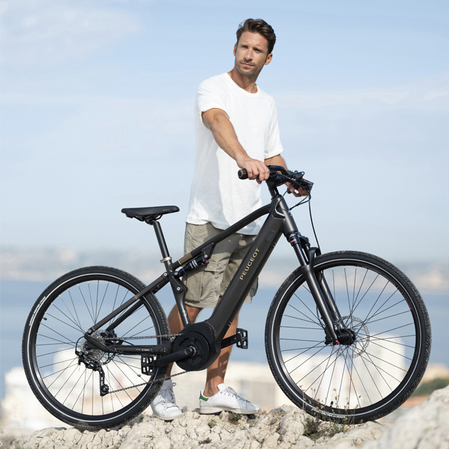 Cyclist standing with his electric trekking bike eT01 powertube