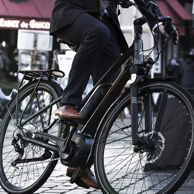 Man on a Peugeot electric Trekking bike driving on a paved street.
